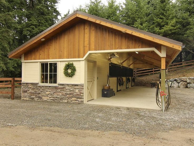 Open breezeway barn with board and batten gable ends, stone wainscot wrap and powder-coated stall fronts. This shedrow barn couldn't be any more perfect!  -ontfequestrian