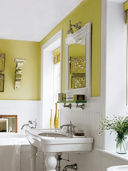 plain bathroom mirror framed in door casing and hung over a pedestal sink in a yellow and white bathroom, with a pewter-finish sconce hanging over the mirror