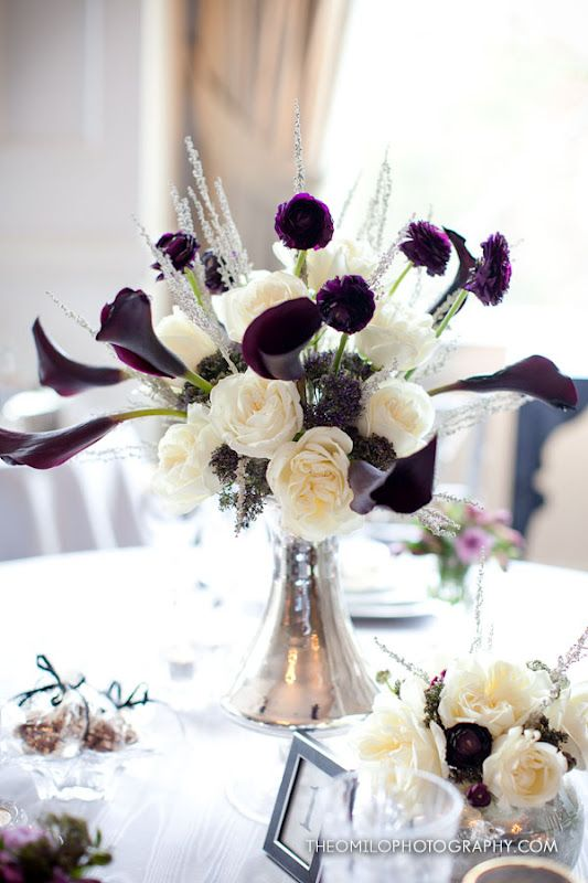 deep eggplant Calla Lilies  ivory Roses, purple Ranunculus, Heather & accents of Silver Queen in an Art Deco mercury glass vase.