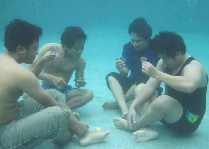 Four guys playing poker underwater