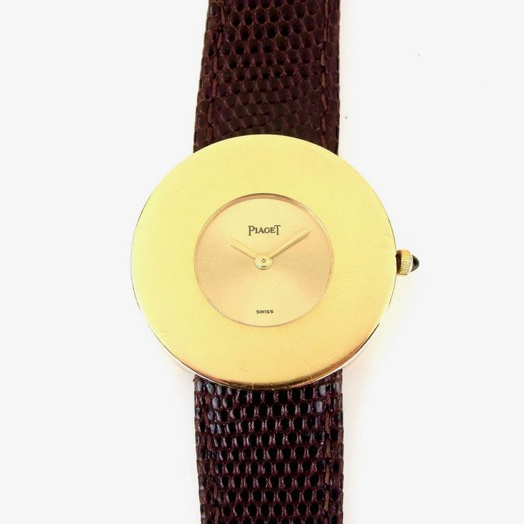 Piaget 18 ct yellow gold ultra-thin lady's watch. Piaget 18 ct yellow gold ultra-thin lady's watch. Ref. 99001. Circa 1970s. Manual wind movement. The round 30 mm case with gold dial, gold hour and minute hands, oversized gold bezel and onyx set crown. On a brown lizard skin Hirsch strap with pin buckle clasp.