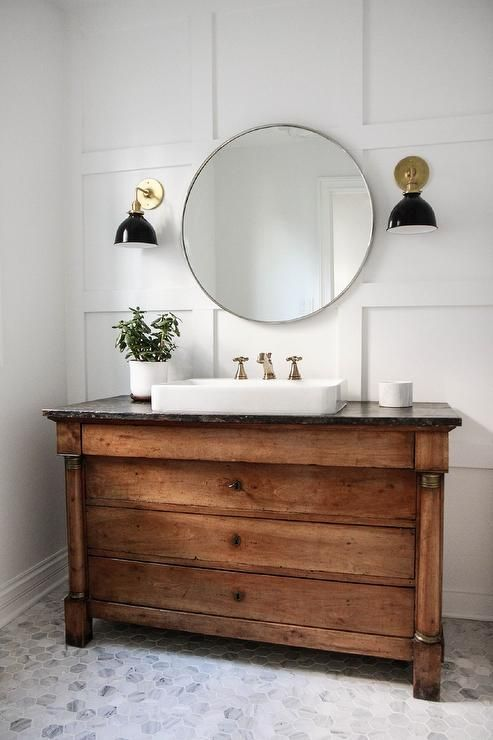 Sat on Carrera marble hexagon floor tiles, a repurposed wood dresser fitted with a rectangular vessel sink accented with an antiqued brass faucet positioned under a circular vanity mirror flanked by black and gold downturned sconces mounted on a board and batten trimmed wall in this lovely cottage bathroom.