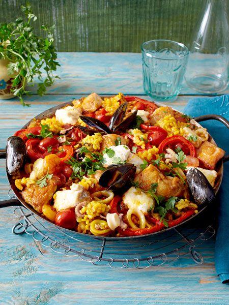 Paella mixta  350 g TK-Frutti-di-mare (Meeresfrüchtemischung) 400 g TK-Miesmuscheln mit Schale 1 Hähnchenbrust (ca. 600 g; mit Haut und Knochen) 3 EL Olivenöl 500 g Fischfilet (z.B. Seehecht) 2 rote Paprikaschoten 1 Zwiebel 2 Knoblauchzehen Salz, Pfeffer 2 Döschen (à 0,1 g) Safranfäden 1 Glas (400 ml) Fischfond 175 ml Orangensaft 1 Dose (425 ml) Kirschtomaten 250 g Paellareis 4 Stiele Petersilie Alufolie