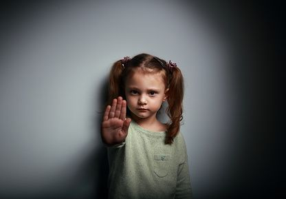 Kid girl showing hand signaling to stop useful to campaign against violence and pain on dark background with empty copy space