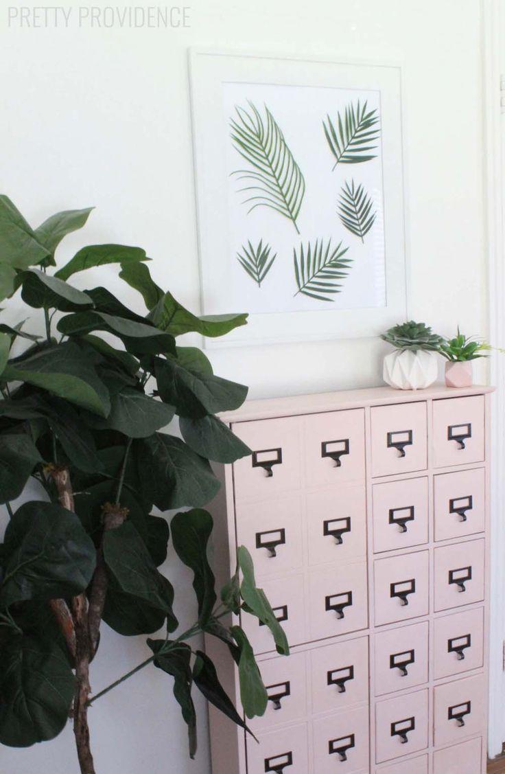DIY Wall art met tropische bladeren. Perfect voor een clean minimalistisch urban jungle interieur! (En hóé mooi matcht het groen van de bladeren met de blush roze apothekerskast?) // via Pretty Providence