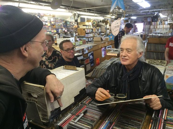 Jimmy Page chatting with the owner of a famed vinyl shop in Boston, April 2014. He collects albums as does photographer Ross Halfin, next to JP in glasses.