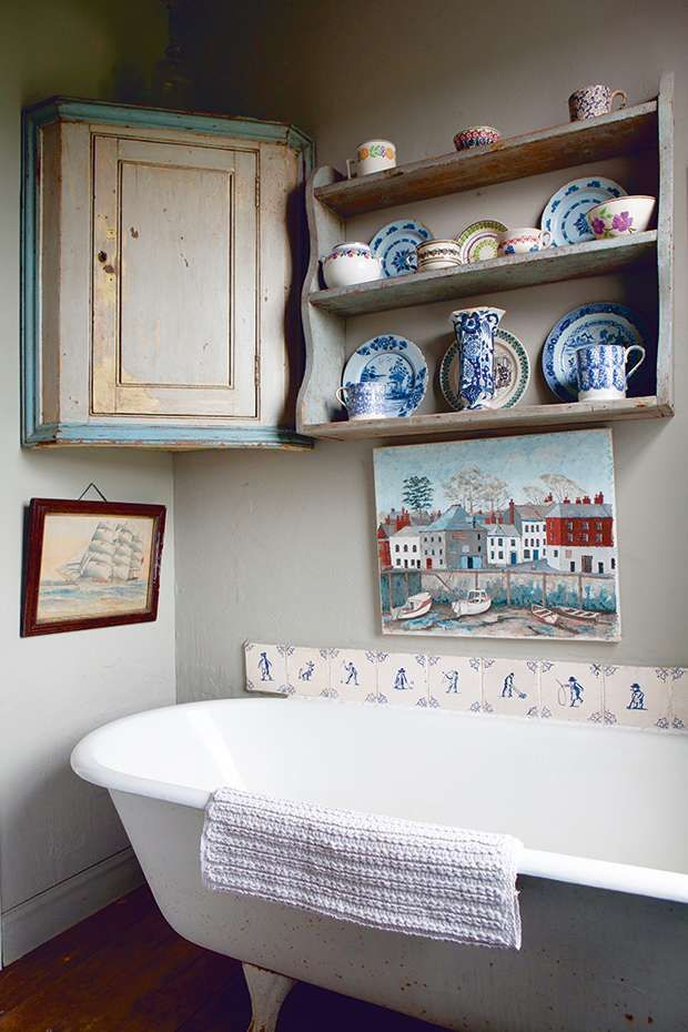 A painting of the bay in Padstow, Cornwall brings colour into the bathroom, and some of Jane's spongeware pottery collection is displayed on antique shelves