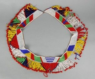 A married woman's multi-coloured beaded waist-belt (part of overall costume) consisting of a narrow band of vegetal fibre to which is attached a thick fringe of beaded pendant strands.