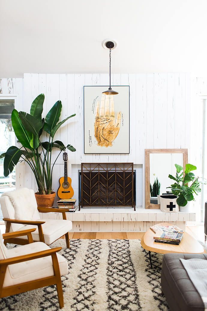 Contemporary bohemian living room style with a herringbone fireplace cover, plants, midcentury accent chairs and a Moroccan-inspired area rug.