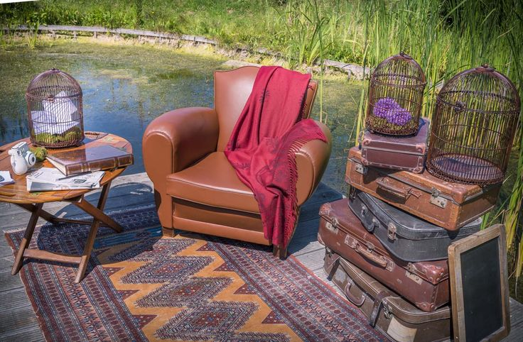 Coin livre d'or. Thème campagne champêtre. Valise vintage en cuir, cage à oiseaux, fauteuil, ardoise, en location chez D DAY DECO.