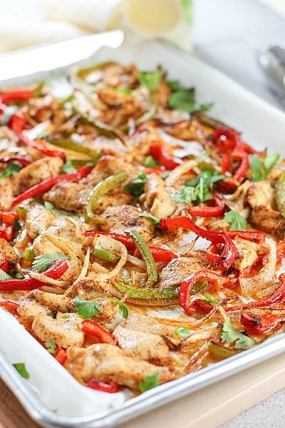 Sheetpan Fajitas 1 pound chicken breasts - sliced thinly 1 red pepper - sliced 1 green pepper - sliced 1 yellow pepper - sliced 1 onion - halved and cut in slices ¼ cup olive oil 2 teaspoons chili powder 1 teaspoon cumin ½ teaspoon garlic powder Pinch of chili flakes 1 teaspoon salt ½ teaspoon ground pepper