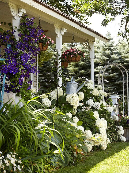 Gingerbread corbels, an arbor, and decorative touches such as the galvanized watering can hanging from a hook bring the vintage charm inside the home to the exterior!  http://www.bhg.com/decorating/decorating-style/country/house-tour--antique-farmhouse/?socsrc=bhgpin112214lushgarden&page=13