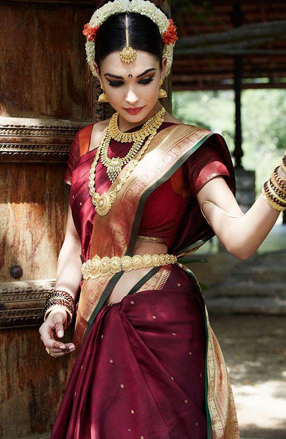 South Indian bride. Temple jewelry. Jhumkis.Maroon silk kanchipuram sari.Braid with fresh flowers. Tamil bride. Telugu bride. Kannada bride. Hindu bride. Malayalee bride. Amy Jackson for Tanishq.