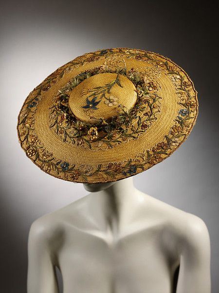 The V says ~ Round, flat straw hat with shallow crown. Embroidered with straw-work flowers on crown and around brim; wreath of straw flowers around crown.