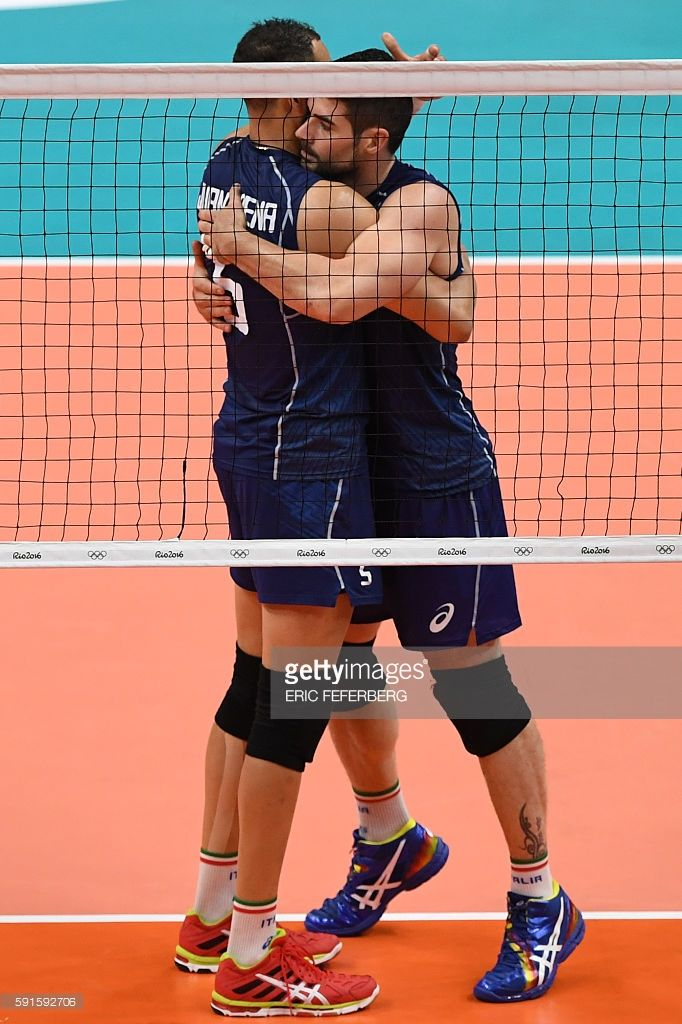 Italy's Osmany Juantorena (L) and Italy's Filippo Lanza hug after scoring during the men's quarter-final volleyball match between Italy and Iran at Maracanazinho Stadium in Rio de Janeiro on August 17, 2016, during the Rio 2016 Olympic Games. / AFP / Eric FEFERBERG