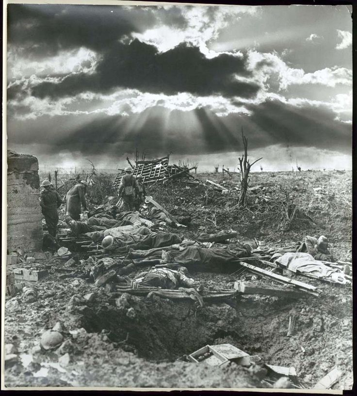 Frank Hurley Australian 1885-1962.   In the middle of a desolate scene of ruins and ravaged trees, a man lies on his stomach, his large boots awkwardly placed. Unlike other soldiers in the photograph, he is not lying on a stretcher. Is he dead? The wounded await the attention of the walking; other figures, wrapped in blankets, are either asleep or dead on their stretchers. Dark clouds obscure the morning sun.  On 12 October 1917, as part of the ongoing Third Battle of Ypres on the Western…