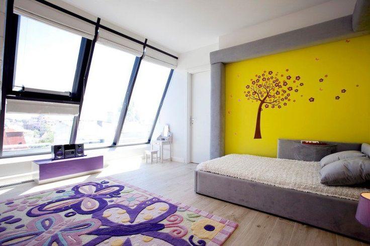 chambre enfants en blanc gris avec tapis à papillons et mur jaune