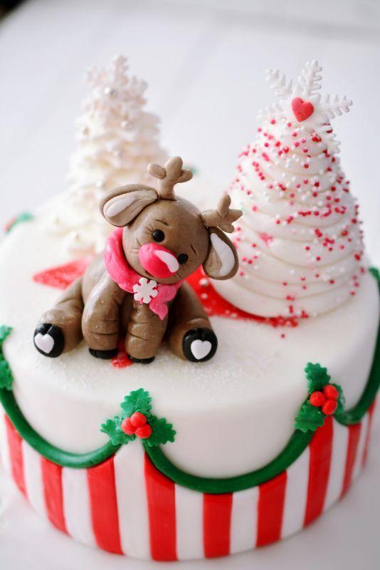 eine Weihnachtstorte im klassisch rot weiß grünen Design und Rentier Lars als cake topper, die Torte zum Basiskurs Motivtorten,