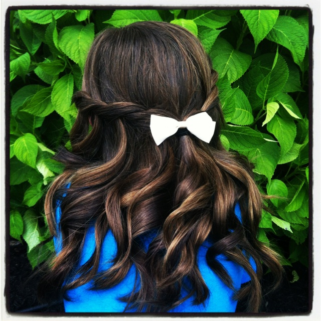 Waterfall braid with loose curls on a 10 year old in front of a hydrangea