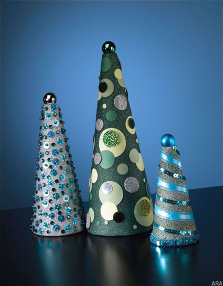 Here's what you may need: various sized foam cones, glitter spray, scrapbook papers, self-adhesive foam sheet, sequins and pins, ribbon, paste and acrylic jewels.  To complete the look of each uniquely designed holiday cone, make a hole in the very top of the cone with a pencil point. Press the neck of a small tree ornament into the hole and secure with a drop of glue. Now you have three beautiful and original cones for a creative and colorful arrangement.