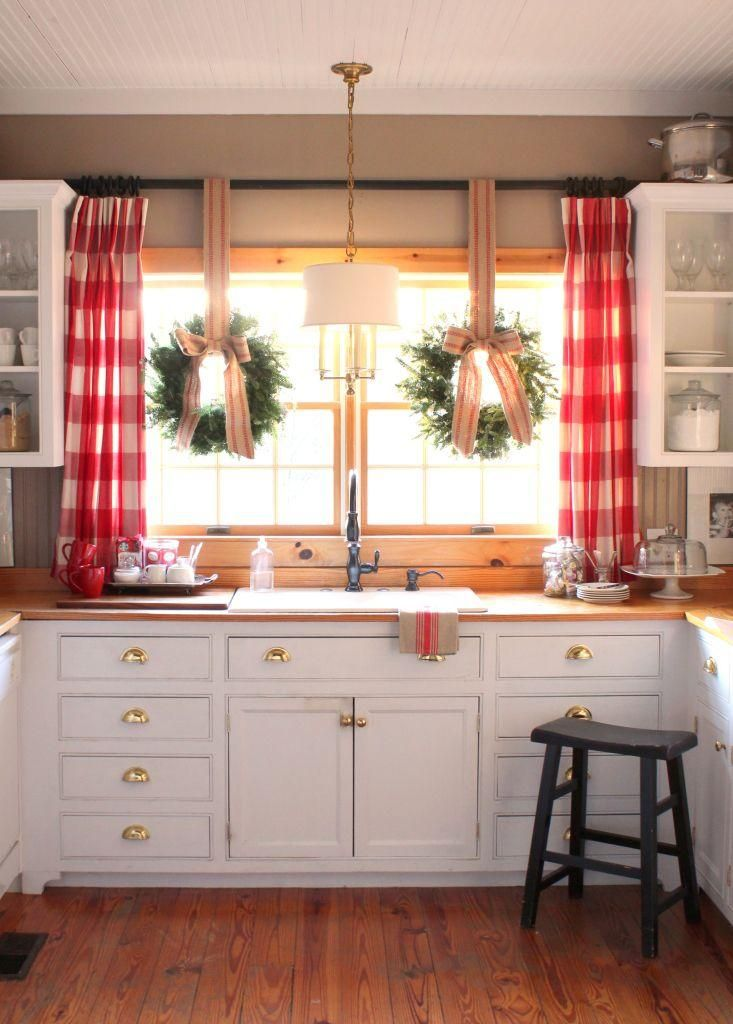 Style idea: Decorate your kitchen for Christmas with red buffalo plaid curtains, and hanging wreaths in the window with jute bows and striped ribbons. Love this Christmas decor idea for the kitchen, especially when paired with the butcher block counters, bright white kitchen cabinets, and shiny brass drawer pulls and hardware. So festive and pretty!