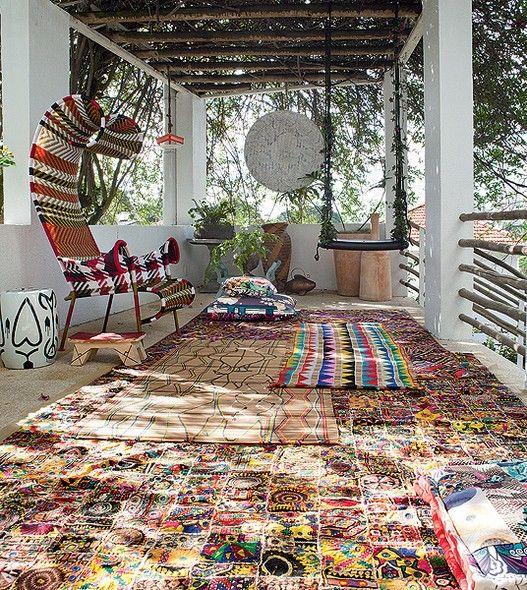 """No chão do terraço, misturam-se tapetes indianos e esteiras indígenas. O balanço e a pérgola cobertos por folhagens também são parte do estilo bohemian. """"Não gosto de jardim muito certinho. Deus é o paisagista"""", diz a moradora Adriana Barra"""