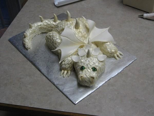 Dragon Cake - A cake I made based on some fabulous tutorials here on Cake Central. The dragon is 100% cake with fondant scales, eyes, claws, and ridge spikes. The wings are gumpaste. Each scale edge was gold dusted.