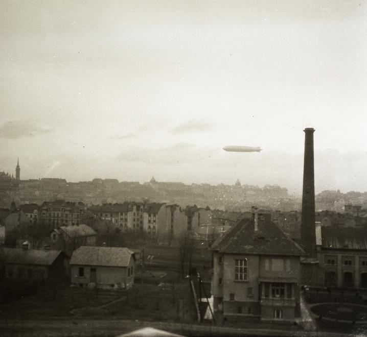 előtérben az Ügyész utca, jobbra a vízművek épülete az Istenhegyi útnál. A Kék Golyó utca és a Nagyenyed utcai házak hátterében a budai Vár és a Graf Zeppelin léghajó.