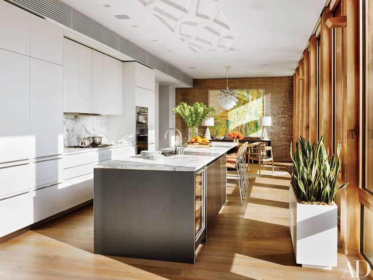Design duo Dufner Heighes chose marble surfaces in this Manhattan penthouse kitchen, which complement Bulthaup cabinetry. The space is equipped with Miele wall ovens, a Gaggenau cooktop, Dornbracht sink fittings, and a Sub-Zero wine refrigerator; the Suite NY stools are clad in a Holland & Sherry fabric. In the breakfast area, the painting is by Tom Cassidy, and the credenza and Tai Ping carpet were custom made.