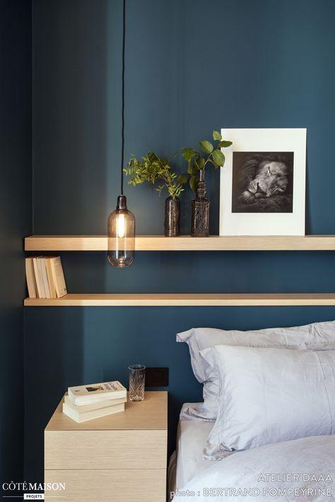 D'élégantes étagères en bois ont été placées au-dessus du couchage en guise de tête de lit.
