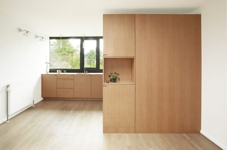 The niche opens up the large and bright surface of the cabinet system toward the living room.
