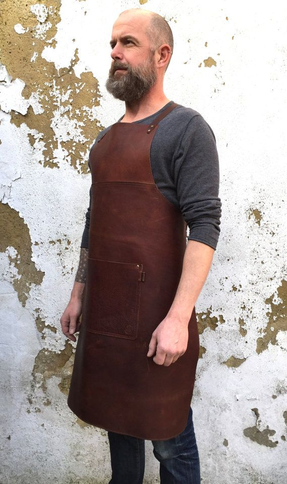Leather apron in a robust veg tan leather.   **** PLEASE NOTE: This apron now comes in the colour shown in the swatch picture, NOT the colour shown on the model, same leather slightly redder in tone ****    Warm red Cognac tones in colour, supple in texture, this beast of an apron is designed for artisans and artists alike, silversmiths, chefs, barbers, welders.......  Crafted to fit the body snuggly, with an adjustable cross back strap design. This strap design makes the apron very…