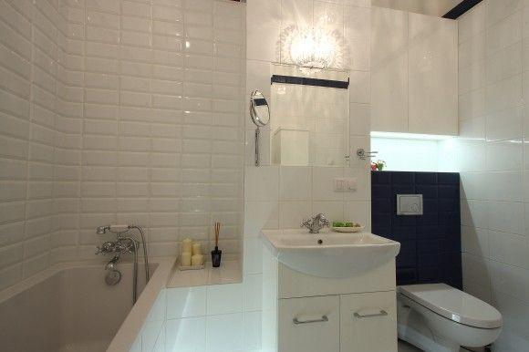 Białe i niebieskie płytki-cegiełki w połączeniu z kryształowym oświetleniem stworzyły efektowne i nowoczesne wnętrze w stylu…