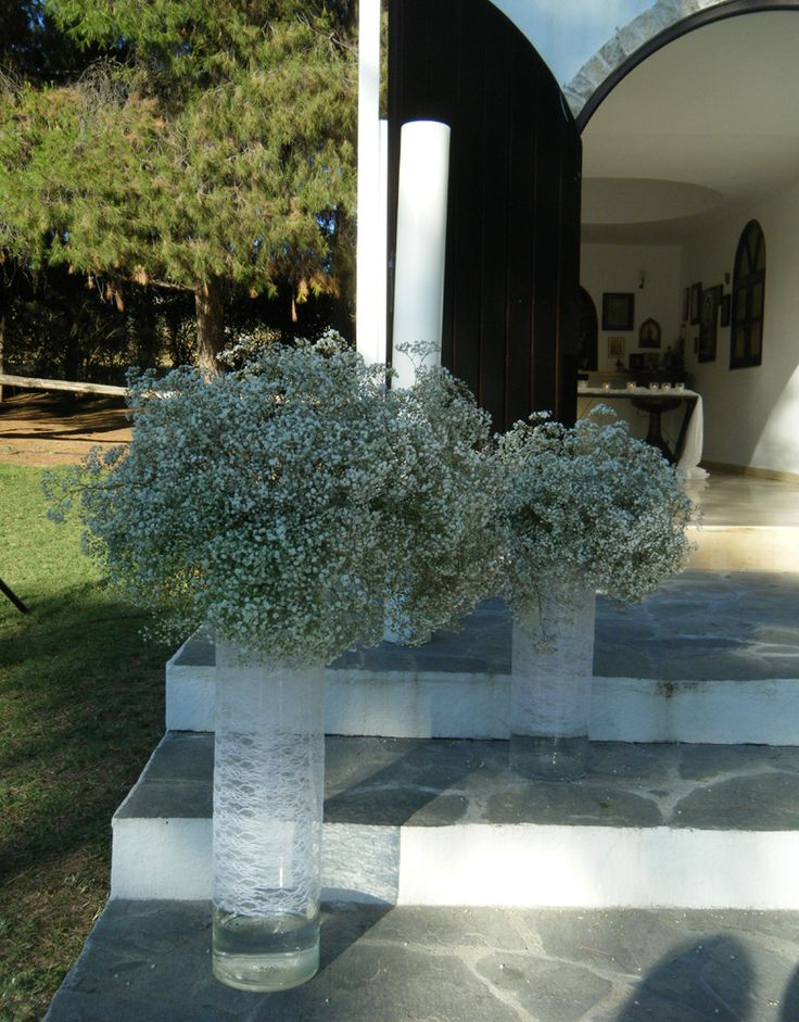 Glass vases wrapped with lace with baby's breath arragements in them