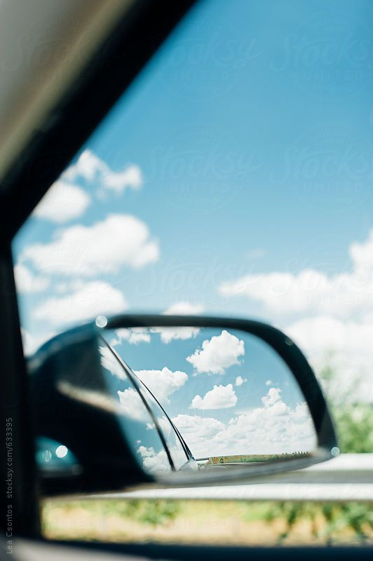View of gorgeous summer clouds in the rearview mirror of a car - Lea Csontos for Stocksy United