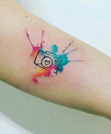 Tatuaje de una cámara de fotos con fondo de acuarela situado en...