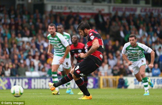 On target: Charlie Austin slots home the penalty in QPR's 1-0 win at Yeovil, which takes them to the top of the Championship