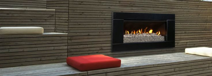 Escea EF5000 outdoor gas fireplace with black surround installed in a wooden outdoor sitting area