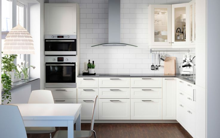 An all-white METOD kitchen with off-white fronts and glass doors, KLARLUFT extractor and RAFFINERAD oven