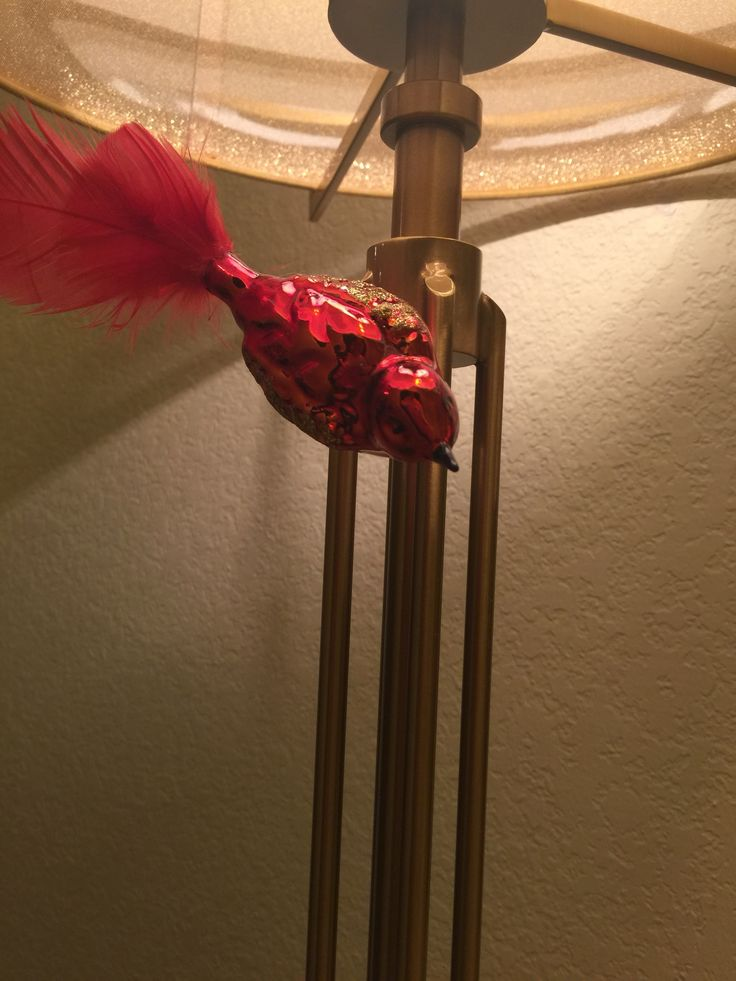 Small Red Bird On A Clip Attached To Lamp Tie In The Holiday Decorations