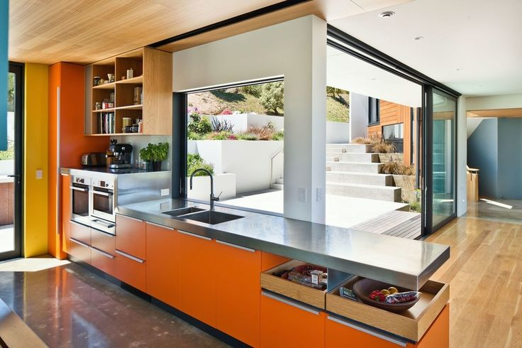 Orange kitchen cabinetry in new home by Parsonson Architects