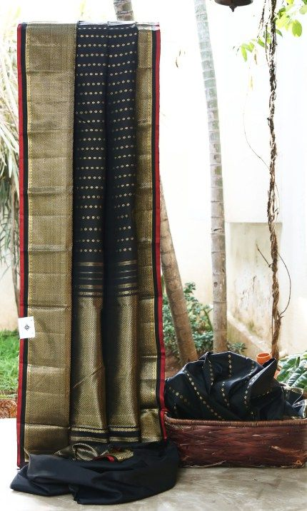 CHARMING BLACK WITH INTRICATELY WOVEN GOLD ZARI HAS TRADITIONAL GOLD ZARI BORDER AND PALLU. THE CHILLY RED SELVEDGE MAKES THE SAREE SPECTACULAR.