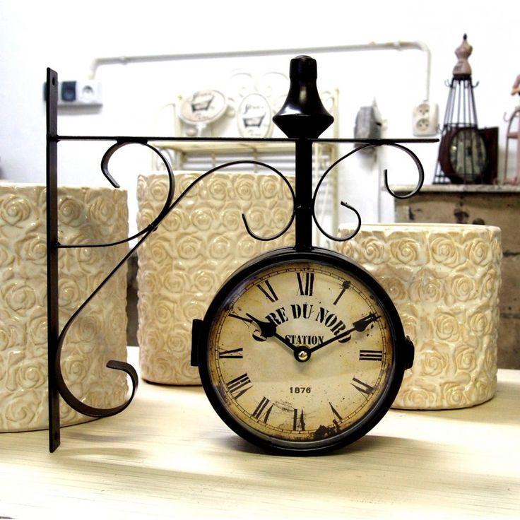 Zegar kolejowy dwustronny o metalowej konstrukcji, lekko zażółconej tarczy oraz z rzymskimi cyframi.