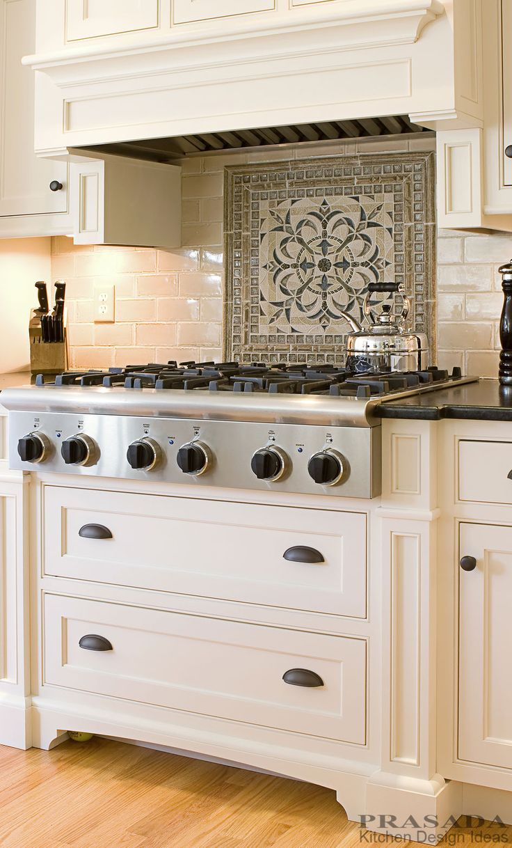 Traditional kitchen.  Off white cabinetry with cook top, decorative backsplash, custom range hood.  www.prasadakitchens.com