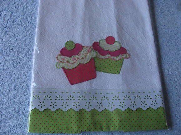 Pano de prato Cupcake <br>Patch Apliquê <br>Estampas fazendo composeê <br>Tecido sacaria <br>Barra em tecido de algodão petit poá <br>Acabamento em bico de poliéster