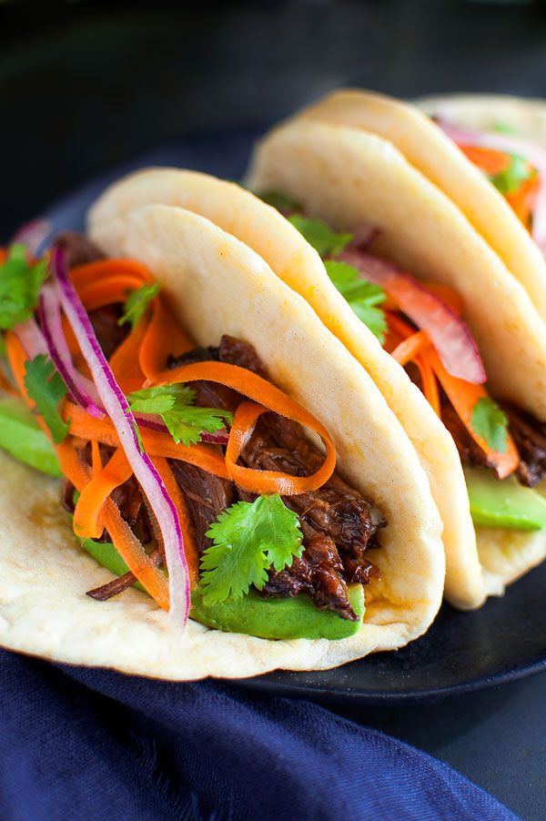Korean Beef Tacos - These beef tacos are juicy, super tender and so easy to make in the slow-cooker. A tangy carrot and red onion slaw is the perfect balance for the sweet-smoky flavor of the beef.   tamingofthespoon.com