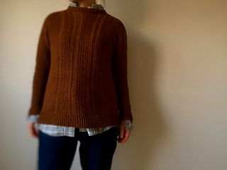 Ryo is a simple seamless pullover, but the construction is very unique. Shoulder saddles are worked directly after neck rib and short rows, then stitches are picked up to from front and back. They are joined at underarm and worked in the rnd to the bottom. The sleeve stitches are picked up and the sleeve cap is shaped with short-rows, then worked in the round from the top down. Caliper Cables adorn the front, back yoke, and sleeves to neck, with very flattering vertical lines.