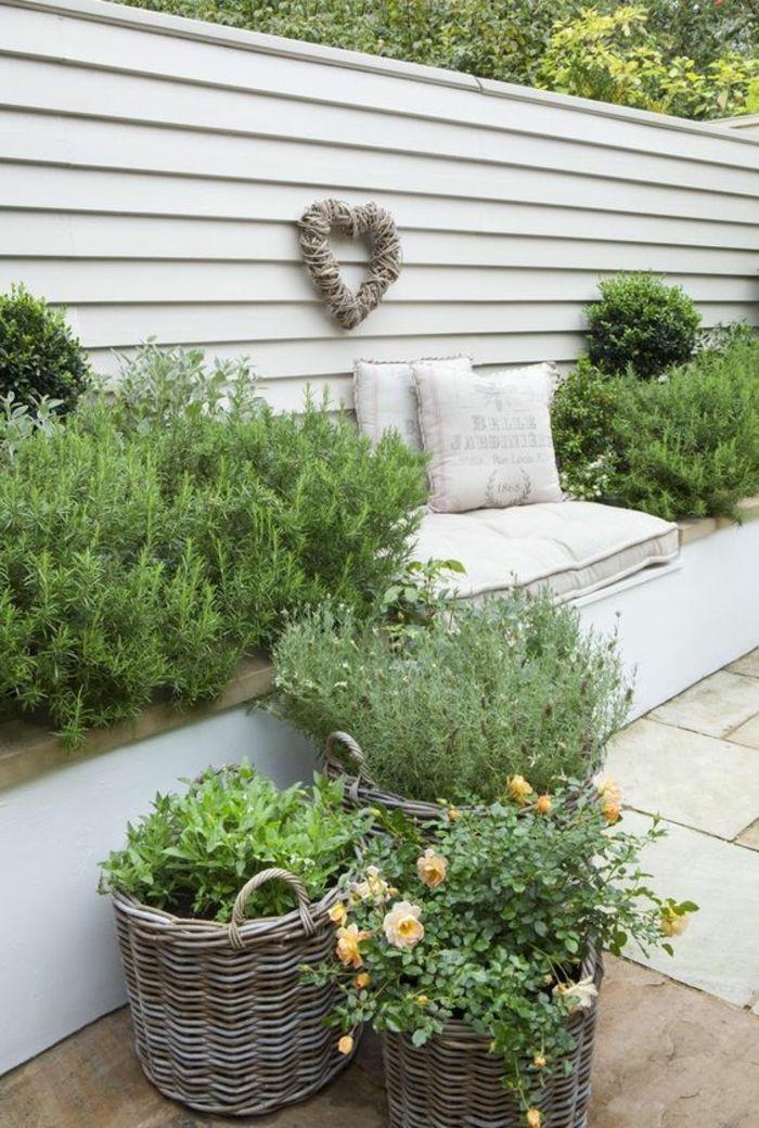 divano da giardino rivestito con cuscini bianchi, appendiabiti color crema decorato …