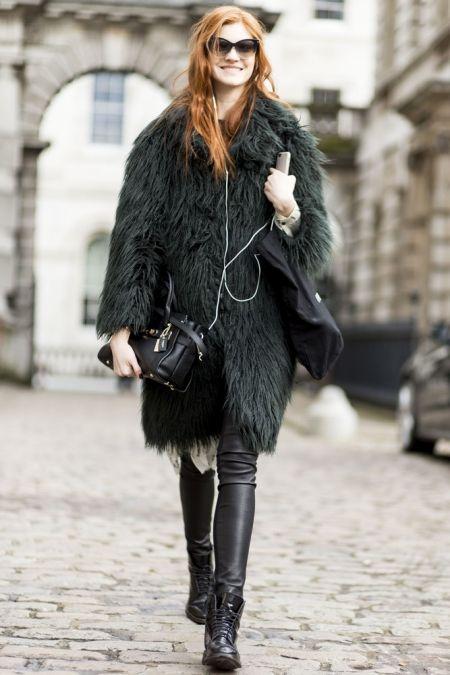 Ruda dziewczyna ubrana w skórzane spodnie, wiązane buty i płaszcz z futra.