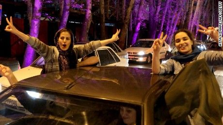 Caption:Women sitting in a car flash the 'V for Victory' sign as they celebrate on Valiasr street in northern Tehran on April 2, 2015, after the announcement of an agreement on Iran nuclear talks. Iran and global powers sealed a deal on April 2 on plans to curb Tehran's chances for getting a nuclear bomb, laying the ground for a new relationship between the Islamic republic and the West. AFP PHOTO / ATTA KENARE (Photo credit should read ATTA KENARE/AFP/Getty Images)